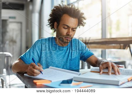 Stylish Unviersity Student Sitting Indoors In Spacious Room Having Solemn Expression Looking In Book