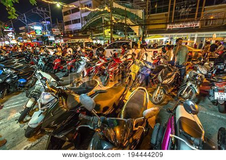 Patong, Phuket, Thailand - January 1, 2016:many scooters parked on sidewalk and street, crowd of tourists, local people with bikes and congested traffic during new year in Patong, famous for nightlife