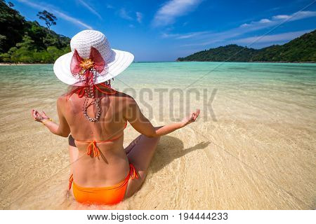 Beautiful and peaceful woman doing yoga meditation in lotus pose in orange seasuit on the beach at Mu Ko Surin National Park, Andaman Sea, Thailand, Asia.