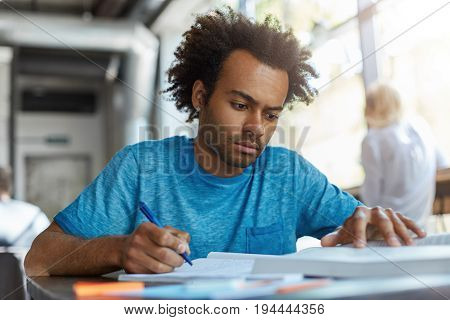 Mixed Race Male Student With Crisp Hair Wearing Blue T-shirt Doing His Home Assigment While Sitting