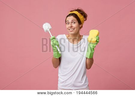 Indoor Shot Of Young Attractive Housewife In Casual Clothes Wearing Gloves Holding Washing Spray And