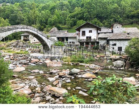 Landscape of Fondo township near Traversella Piedmont with ancient stone bridge and Chiusella river