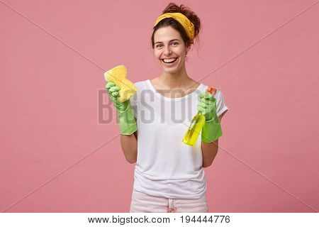 Portrait Of Happy Female Doing House Duties Wearing Rubber Gloves And Holding Detergent With Sponge