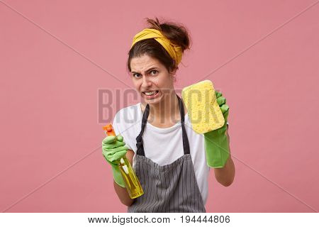 Cute Housemaid Looking With Disgust Into Camera Wearing Apron, Yellow Headband And Green Rubber Glov