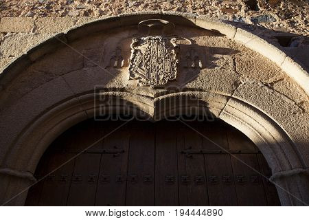 Caceres palace facade. Door with carved shield. Coat of arms Illuminated by last ray of sun