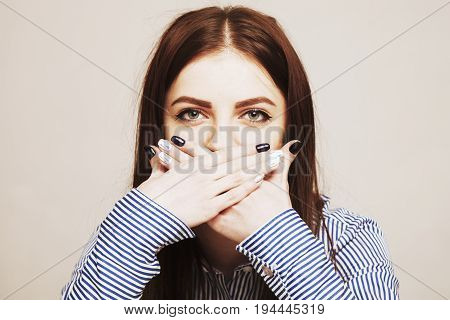 I will not tell you anything. Silence tabu secrety mystery communication concept. Woman covering the mouth with her hands. (Gestures psychology body language concept)