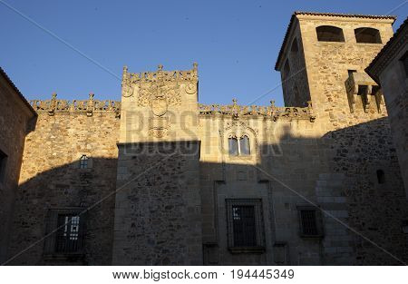 Golfines Palace at sunset. Coat of arms Illuminated by last ray of sun Caceres Spain