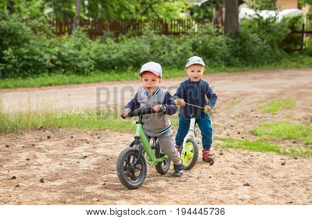 Two happy little boys or toddler 2-3 years outdoors with balance bikes