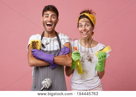 Excited Man In Casual Clothes Keeping Hands Crossed Holding Dirty Sponge Rejoicing His Work. Smiling