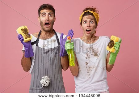 Shocked Male And Female Doing Chores Wearing Casual Clothes Looking With Surprisment At Very Dirty F