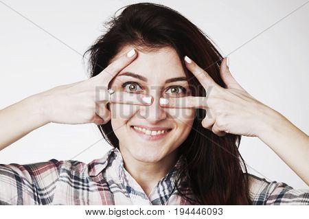 Woman peeking behind her hand (Gestures psychology body language concept)