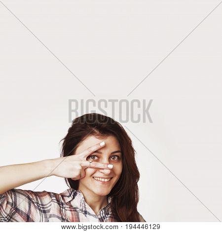 Woman peeking behind her hand through fingers