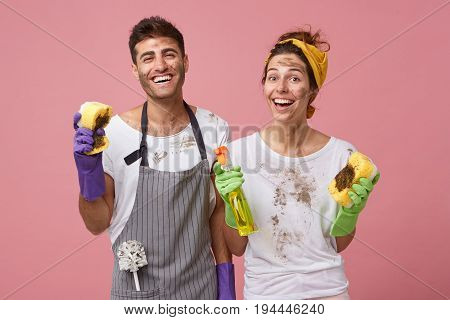 Glad Husband And His Wife Being Untidy After Cleaning House Holding Dirty Sponges And Detergent Work