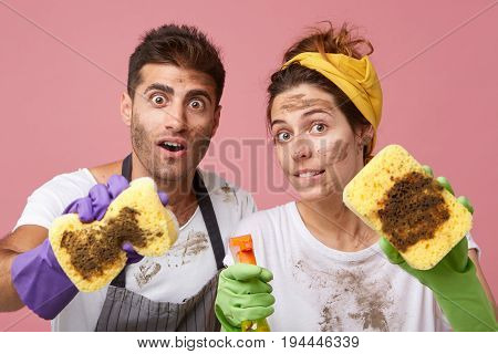 Astonished Female And Her Husband With Dirty Faces Showing Very Dirty Sponges After Cleaning Window