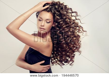 Brunette  girl with long  and   shiny curly  hair .  Beautiful  model woman  with wavy hairstyle .