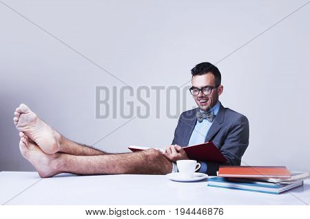 Successful happy young businessman with bare feet works in office. (Boss business rules officialdom concept)