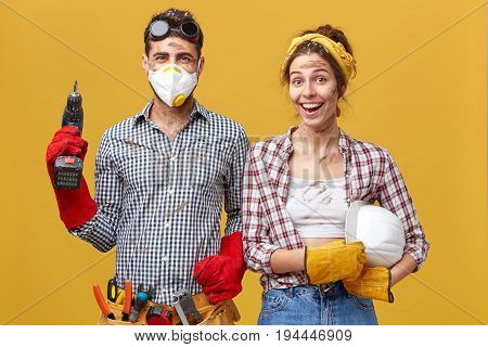 Positive Handyworkers Wearing Casual Protective Clothes Holding Builduing Equipment Smiling Sincerel