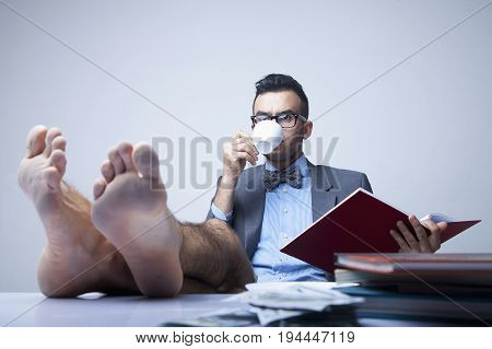 Successful happy young businessman with bare feet working in office. (Boss business rules officialdom concept)