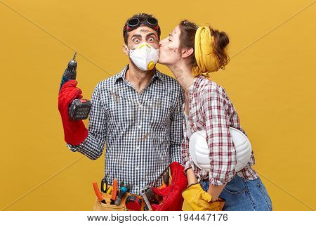 Pretty Female Kising Her Husband In Cheek Being Thankful To Him For Repearing Her Wardrobe. Surprise