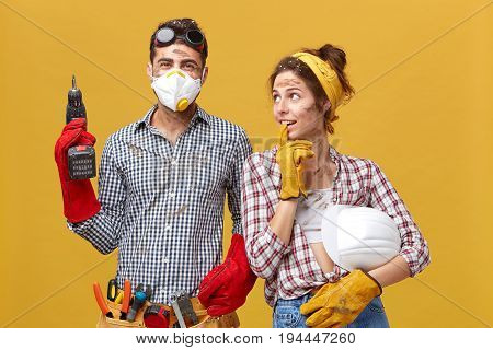 Woman In Casual Shirt And Jeans Holding Hardhat Looking Attentively At Her Husband Who Is Builder Wo