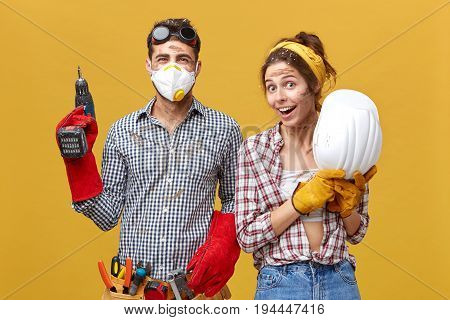 Portrait Of Positive Male With Drilling Machine And Tool Belt And His Female Colleague Holding Hardh