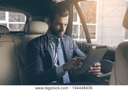 Young business person test drive new vehicle usng digital device
