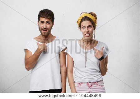 Indoor Shot Of Dissatisfied Male And Female Wearing Casual Clothes Frowning Thier Faces And Pointing