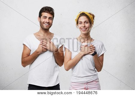 Kind-hearted Man And Female Dressed In White T-shirts Holding Their Hands Togehter On Chest Being Th