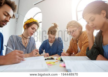 Interracial College Friends Meeting Together Sitting At Table Having Serious Look In Their Books Rea