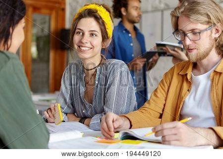 Happy Beautiful Woman In Shirt Discussing Something With Her African Friend Sitting Near Her Groupma