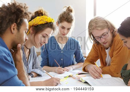 Five Mixed Race College Students Sitting Together At Table Underline Important Information In Books