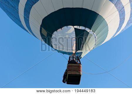 Colorful hot-air balloon is inflated for flight against a blue sky