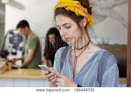 Cute Female Wearing Yellow Scraf On Head And Casual Shirt Sitting In Cafe Using Smart Phone Sending