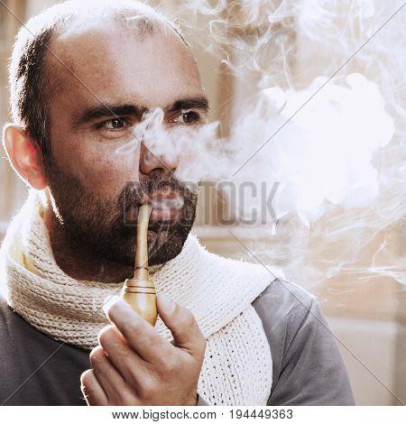 young businessman enjoying pipe smoking (tobacco smoke addiction concept)