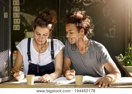 Two Friends Of Different Races Sitting Together At Terrace Working With Papers And Books Writing Wit
