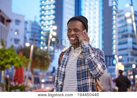 Portrait Of Handsome Black Male In Casual Wear And Rucksack Standing Over Night City Background Call