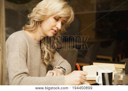 young beautiful girl is preparing for exam (Education knowledge exam success concept)