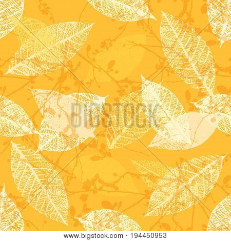 A seamless background pattern of vector skeleton leaves and abstract tree branches in warm yellow, autumnal repeat print