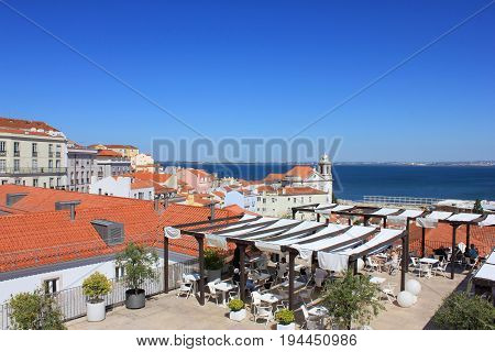 Panoramic Portas do Sol viewpoint and open air terrace cafe in Lisbon, Portugal. Rooftop view of Alfama old town historical district on summer time