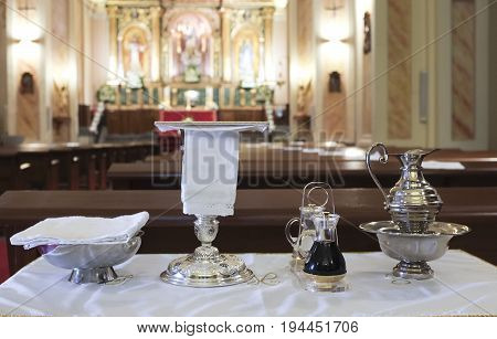 Catholic liturgical objects displayed over table at church. Chalice communion wafers wine water ewer and basin
