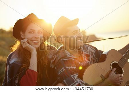 Lifestyle, Relax Time And Holiday Concept. Smiling Man Singing Serenade To His Lady Playing Guitar W