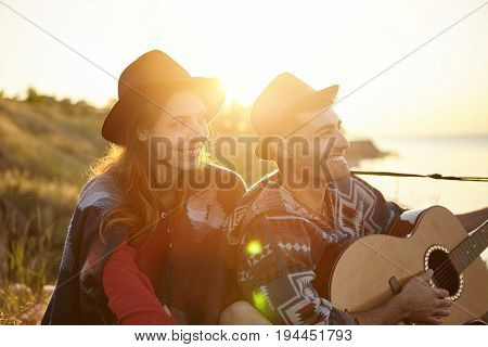 Romantic Man With Guitar Singing Serenade To His Girlfriend Oudoors. Lovely Couple In Love Sitting T