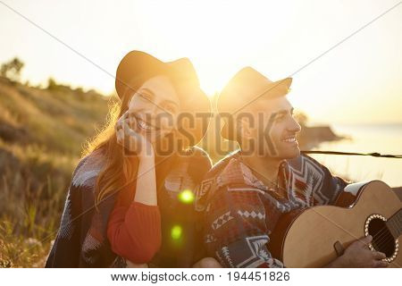 Young Male With Bristle Wearing Black Hat Holding Guitar Singing Songs About Love To His Girlfriend