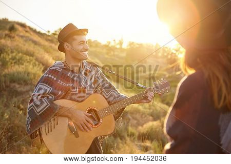 Cheerful Talented Male Playing Guitar Enjoying His Hobby Standing Near His Lover Demonsrtating His T