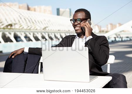 Cheerful Businessman In Eyewear Sitting At White Desk Speaking With Somebody Over Smart Phone Workin
