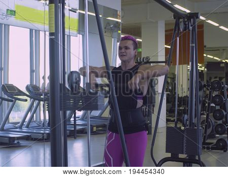 Very strong women doing body building exercises in the fitness studio