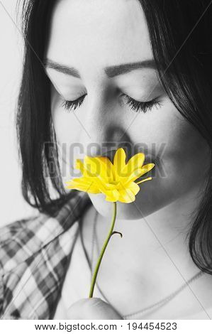 Close-up portrait of Beautiful young woman smell a flower. (Pleasure nature vacation)