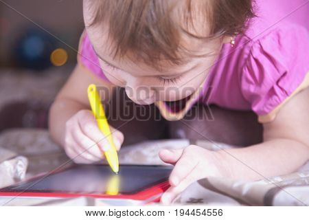 Little business baby girl holding tablet in hands and planning his workday. Humorous picture. Time management business job offer analytics research concept.