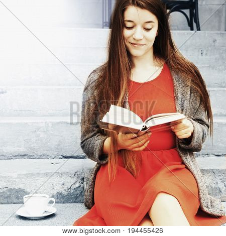 Young beautiful woman reading interesting books in old center of europe city (Knowledge development education success youth concept)