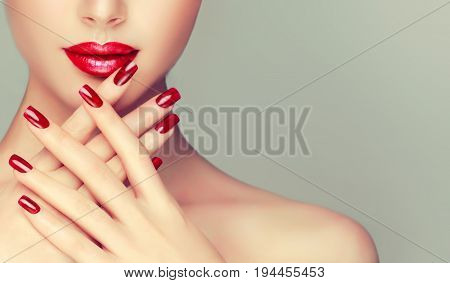 Beautiful girl showing red  manicure nails  . makeup and cosmetics, red lips .